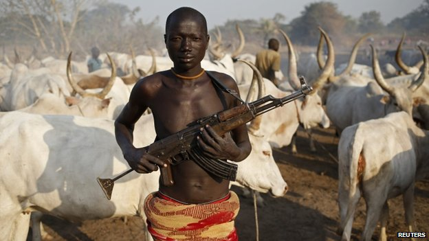 Armed Dinka tribesman in front of a cow herd in Lakes State, South Sudan (14 December 2013)