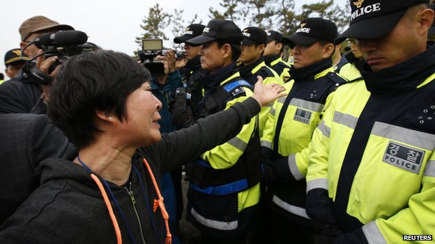 "A family member of a passenger missing after the South Korean ferry ""Sewol"" capsized demonstrates in front of police during a protest in Jindo calling for a meeting with President Park Geun-hye and demanding the search and rescue operation be speeded up, April 20"