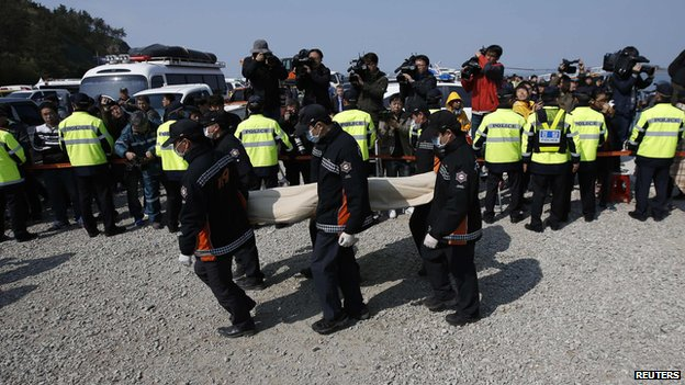 South Korean rescue workers carry the body of a passenger who was on the capsized passenger ship Sewol which sank in the sea off Jindo, at a port where family members of missing passengers gather in Jindo April 20