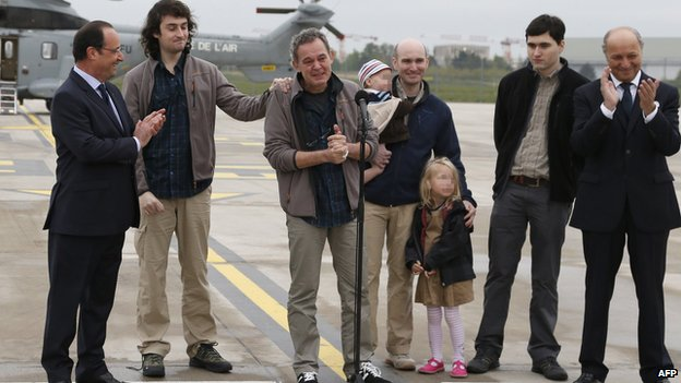 Freed journalists with President Hollande and Foreign Minister Laurent Fabius at Villacoublay air base on 20 April 2014