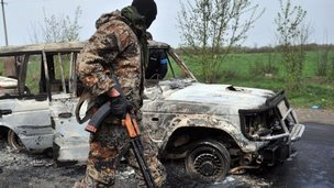 Separatist walks past burnt-out video outside Sloviansk - 20 April