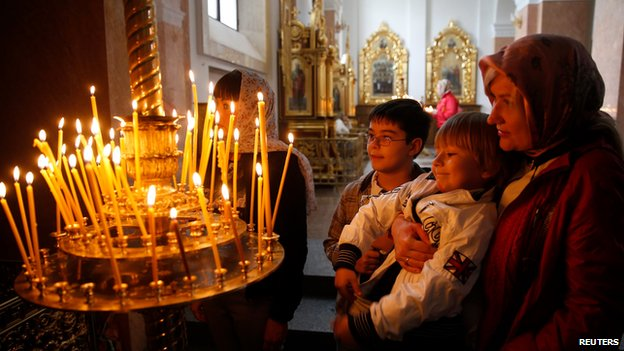 Ukrainian Orthodox believers light candles in a church in Donetsk, eastern Ukraine, on 20 April 2014