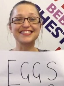 Woman holding a piece of paper with the word eggs written on it
