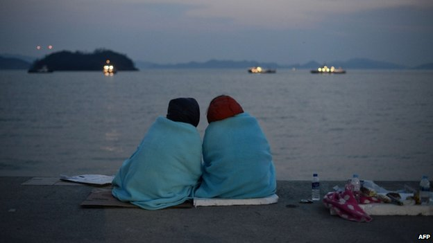 Relatives of victims of the South Korean ferry Sewol sit before the sea at Jindo harbour on 20 April 2014
