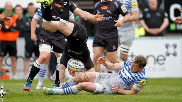 Alex Tait is tackled in the air by Saracens winger Jack Wilson.