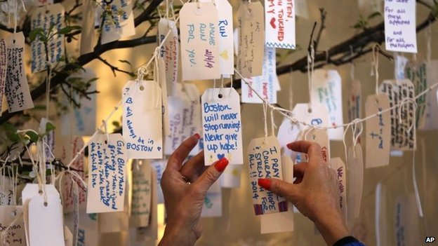 A visitor hangs a message on a tree at the Dear Boston exhibit at the Boston Public Library, 20 April