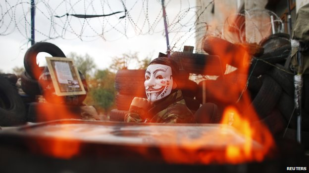 A pro-Russia protester wearing a Guy Fawkes mask sits on a barricade outside a regional government building in Donetsk, in eastern Ukraine April 20