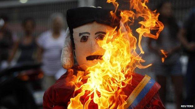 Protesters burn effigies of President Nicolas Maduro, 20 April