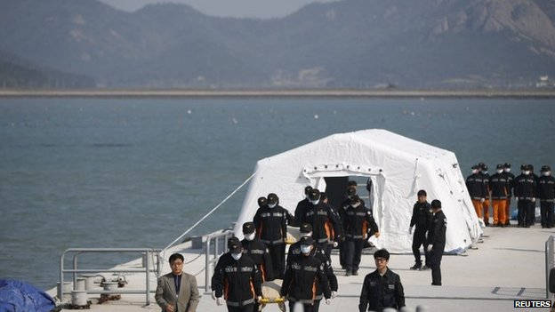 Rescue workers carry the bodies of passengers who were on the capsized Sewol passenger ship, which sank in the sea off Jindo, at a port where family members of missing passengers have gathered, in Jindo on 21 April 2014