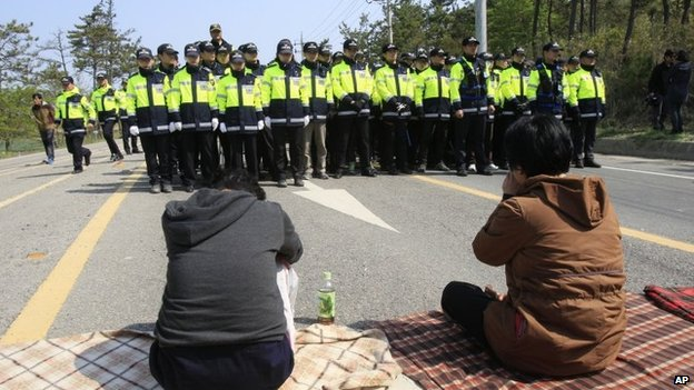 Relatives of missing passengers aboard the sunken ferry Sewol weep in front of policemen as they try to march toward the presidential house to protest the government's rescue operation in Jindo, South Korea, on 20 April 2014