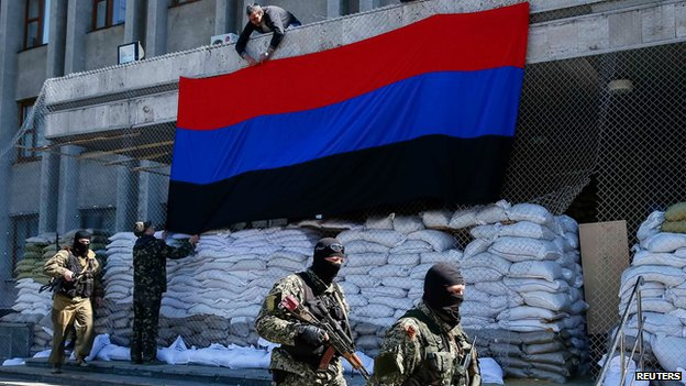 Pro-Russian armed men walk past activists hanging up a 'Donetsk Republic' flag outside the mayor's office in Slaviansk on 12 April 2014