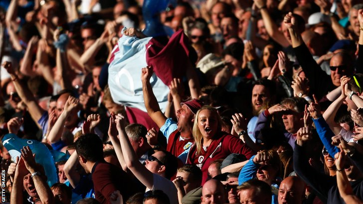 Burnley fans celebrate their team scoring against Blackpool