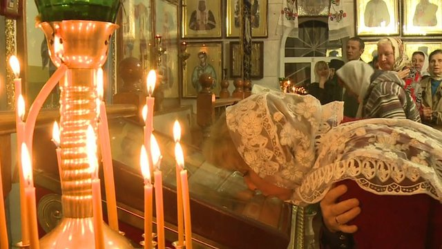 Woman and candles at Orthodox church in Ukraine