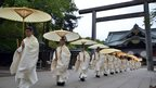 "Shinto priests holding umbrellas walk out from Torii gate as they administer a Shinto rite ""Kiyoharai"" on the first day of the three-day spring festival at the controversial Yasukuni war shrine in Tokyo"