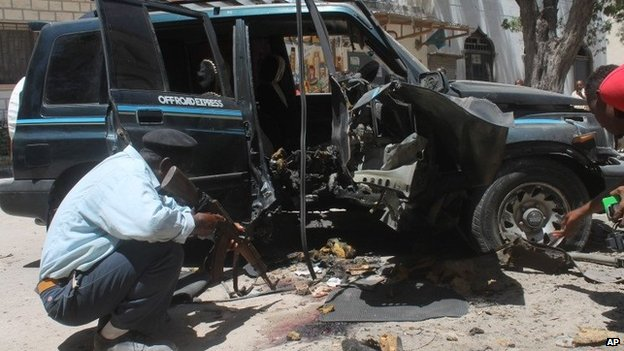 A Somali police officer looks at the wreckage of the car in Mogadishu, Somalia, Monday, April, 21, 2014.