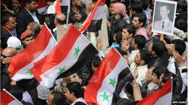 A handout picture released by the official Syrian Arab News Agency (SANA) on April 21, 2014 shows Syrians holding their national flags and a portrait of President Bashar al-Assad during a rally
