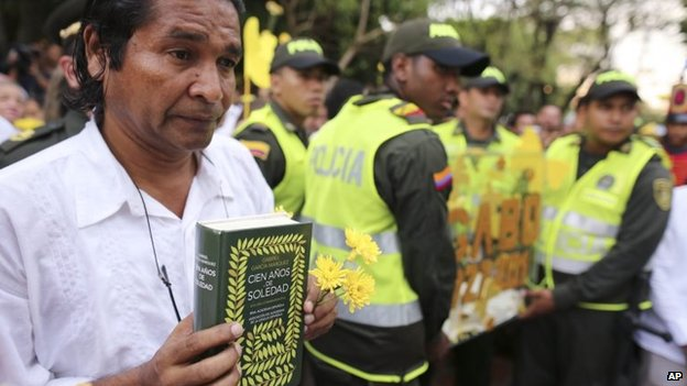 A man holds a copy of One Hundred Year of Solitude during a symbolic funeral in Aracataca, Monday, April 21, 2014.