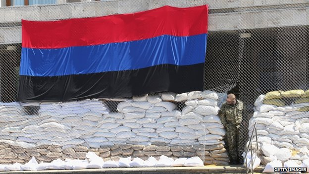 A pro-Russian militant looks out from the barricaded entrance of the city council building on 21 April 2014 in Sloviansk