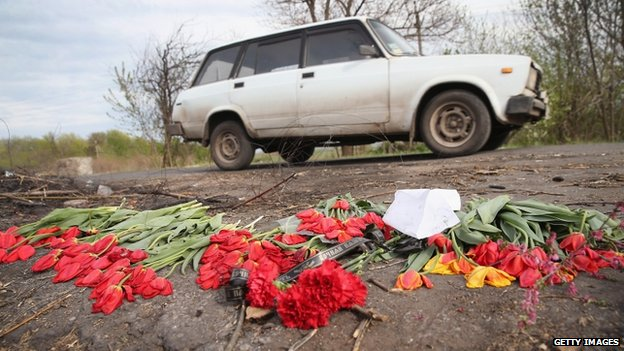 Flowers lay in the road as a memorial to three men shot on Easter Sunday at a checkpoint near Sloviansk