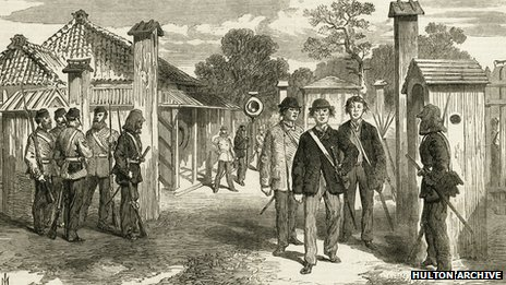 The entrance gate to the city of Yokohama, guarded by European troops at the time of the Meiji restoration, 1868. The three Japanese men walking through the gate are wearing Western style clothes.