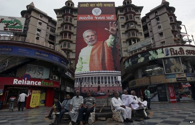 Indians sits on benches in front of a hoarding of India's main opposition Bharatiya Janata Party(BJP) prime minister candidate Narendra Modi at a shopping complex in Ahmadabad.