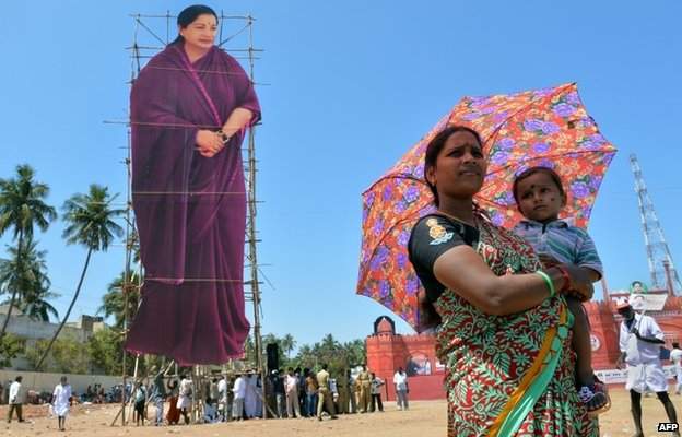 All India Anna Dravida Munnetra Kazhagam (AIADMK) supporter holds a child as she stands beside a giant cut-out of AIADMK Leader and Chief Minister of the southern Indian state of Tamil Nadu J. Jayalalithaa ahead of a public meeting in Pondicherry.