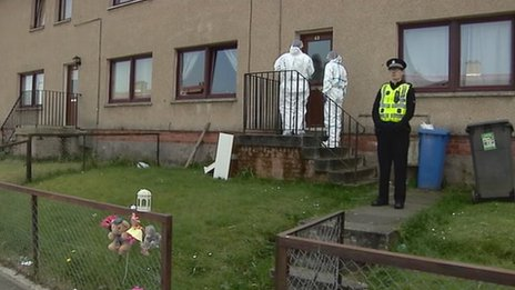 forensic officers and a police officer at the house