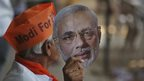 An Indian supporter of main opposition Bharatiya Janata Party (BJP) holds a mask of their prime ministerial candidate their prime ministerial candidate Narendra Modi at an election campaign.