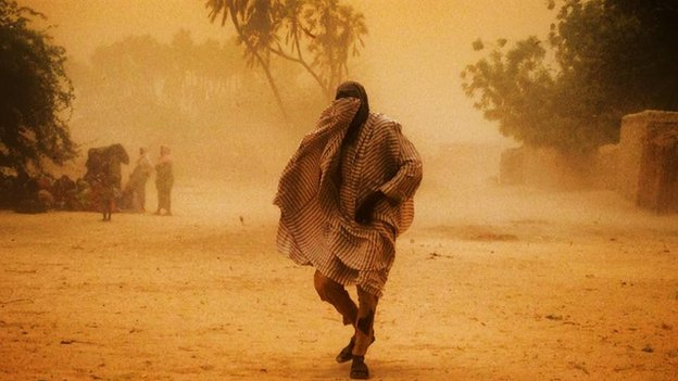 A man from Nigeria in Niger covers his face as he walks through a sandstorm