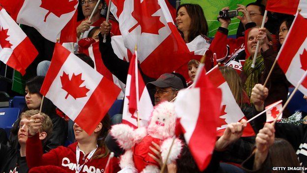 Canadians wave their nation's flag.