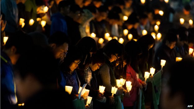 People hold candles at a vigil for students among the missing passengers of a South Korean capsized ferry, in central Ansan on 22 April 2014.
