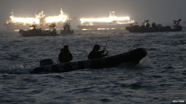 South Korean rescue workers conduct their rescue operation at the area where the capsized passenger ship Sewol sank, as fishing boats emit light, in Jindo on 22 April  2014.