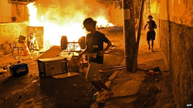 Residents run for cover during violent clashes between protesters and Brazilian Police Special Forces in a favela near Copacabana in Rio de Janeiro