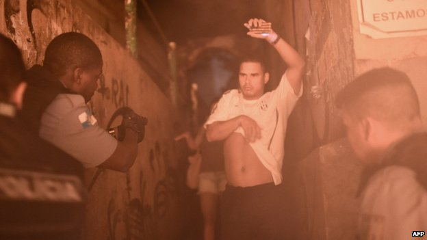 Police detain a man during a violent protest in a favela near Copacabana in Rio de Janeiro, Brazil, on 22 April 2014.
