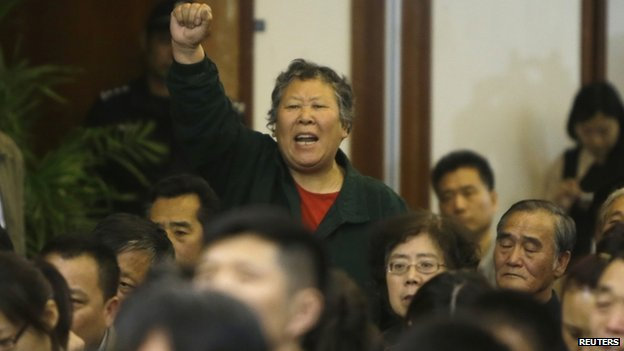 A relative of a passenger aboard MH370 gestures as she shouts at Malaysian representatives during a briefing at Lido Hotel in Beijing (21 April 2014)