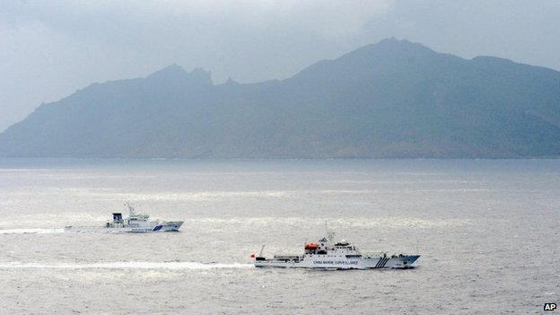 In this 23 April 2013 file photo, a Japan Coast Guard vessel (L) sails along with a Chinese surveillance ship near the disputed islands