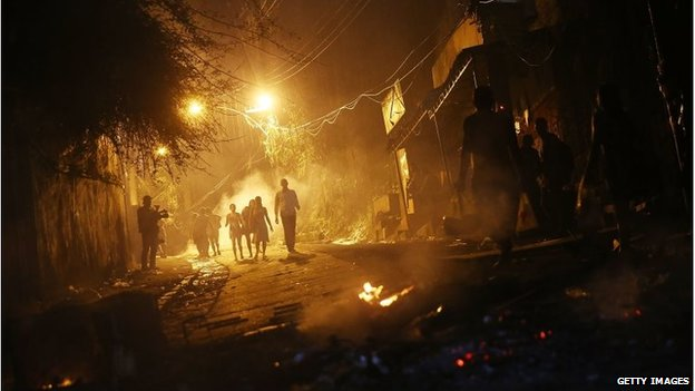 People walk through smoke from fires set by protesters following shootings in the pacified Pavao-Pavaozinho community, just blocks from Copacabana Beach on 22 April, 2014