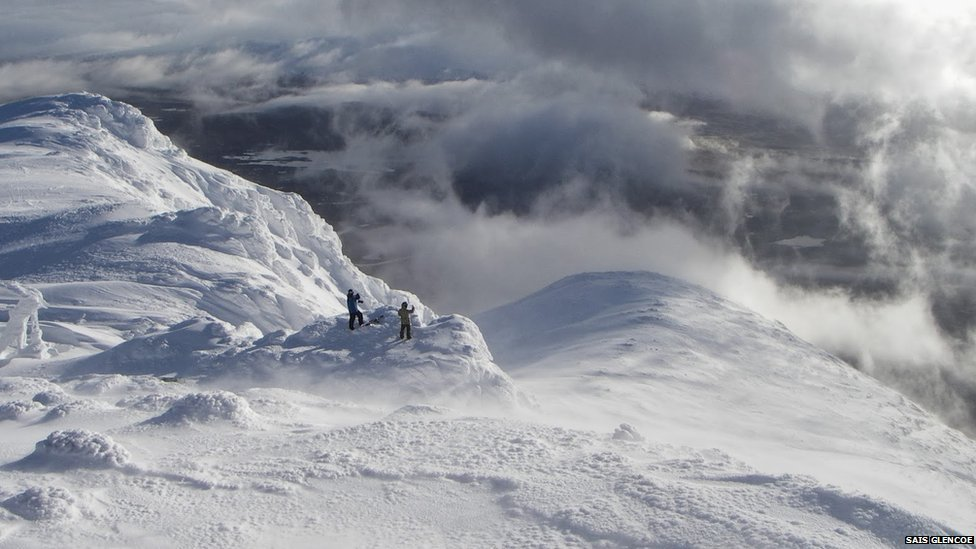 Two walkers take in the view from the summit of Meall a Bhuiridh in Glencoe this winter