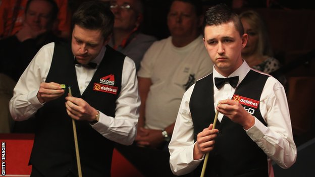 Kyren Wilson assesses a shot while Ricky Walden chalks up