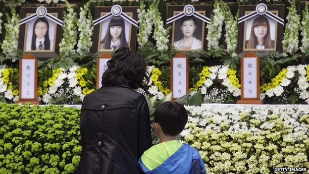 A woman and child pay tribute at a memorial to victims of the sunken ferry at the Ansan Olympic Memorial Hall - 23 April 2014