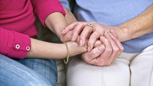 Carer and patient holding hands