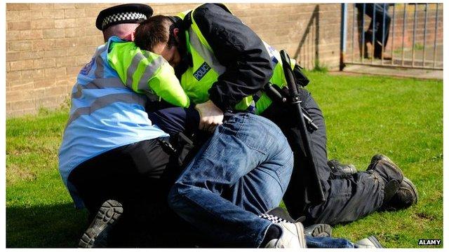 Police restrain a man
