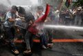 Police train their fire hose on protesters in Manila