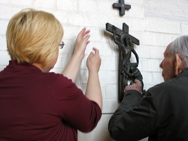 Anne and Fred touching a cross with Jesus on it