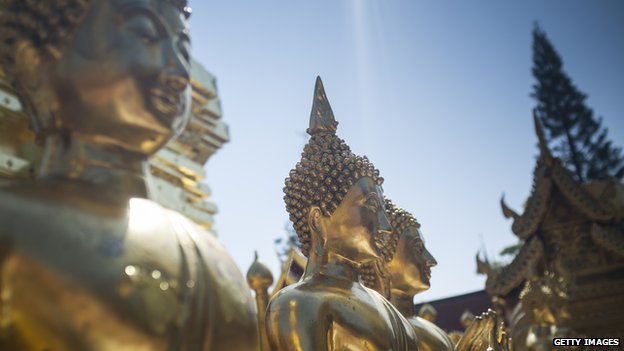 A line of golden Buddha statues at temple in Thailand