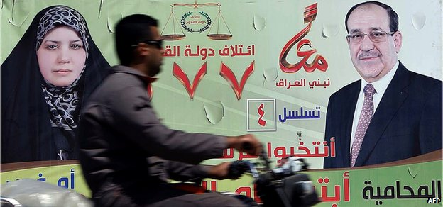 A man rides his motorbike past a large election campaign banner showing Iraqi Prime Minister Nouri al-Maliki in the city of Karbala on 5 April 2014