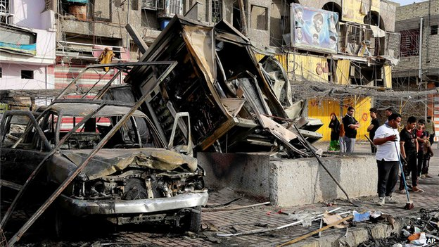 Iraqi civilians cleaning up after a car bombing in the eastern Baghdad district of Sadr City on 11 April 2014.