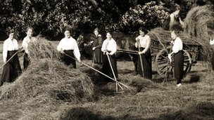 young women raking hay during World War One