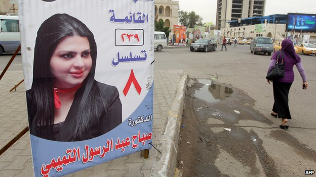 An woman walks past a campaign banner showing female candidate Sabah abed al-Rasul al-Tamimi in the capital Baghdad on 15 April 2014