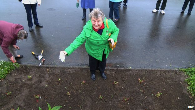 Joan Cadoret planting poppies in St Andrew's Park